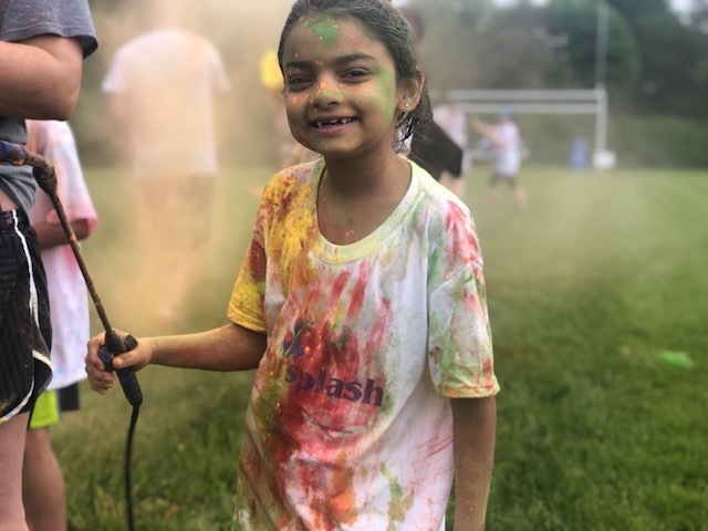 Elementary student having fun with a color sprayer