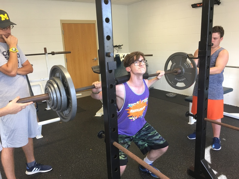 Colin Jones squatting weights with team support