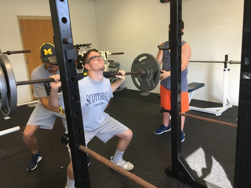 Jake Zanavich squatting weights with team support.