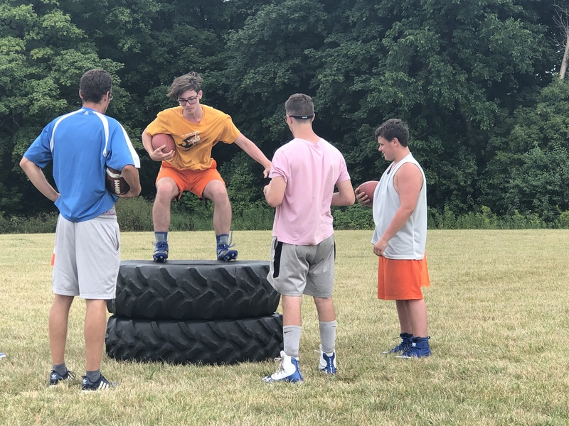 Colin Jones jumping on 2 monster tires with team watching.
